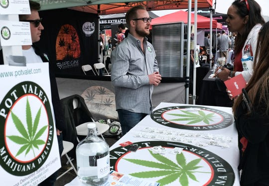 This March 31 photo shows a booth advertising a delivery service for cannabis at the Four Twenty Games in Santa Monica.