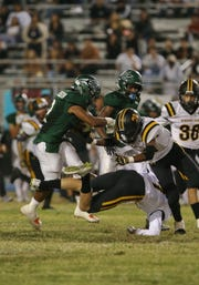 Pacifica High running back Allan Johnson, left, runs over Newbury Park's James Tubb and Christian Middleton during Friday's game. The Tritons won 42-20.