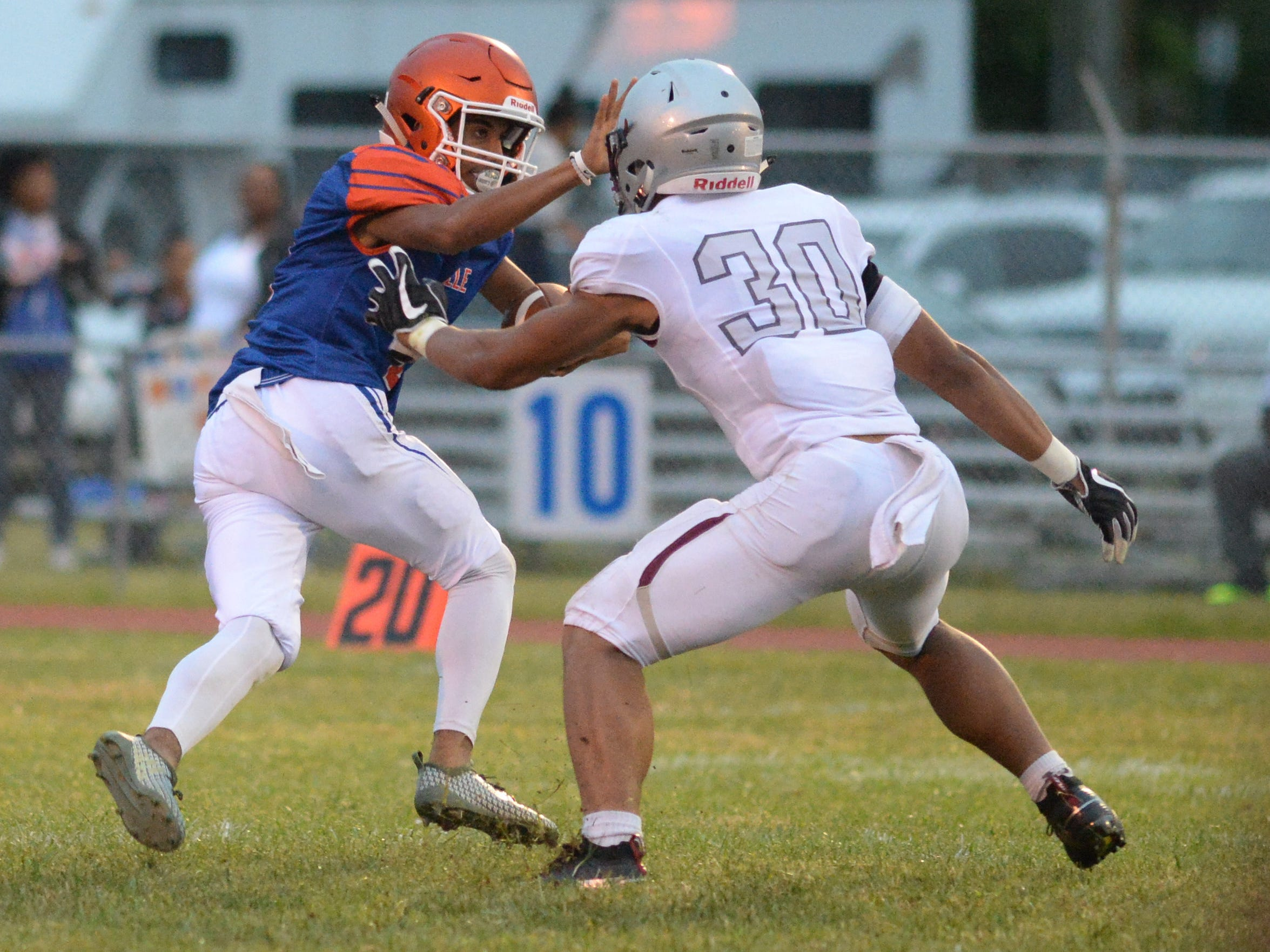 Millville's Eddie Jamison pushes off St. Peter's Prep's Cody Simon as he carries the ball during the season opening football game at Millville Memorial High School, Friday, Aug. 31, 2018.