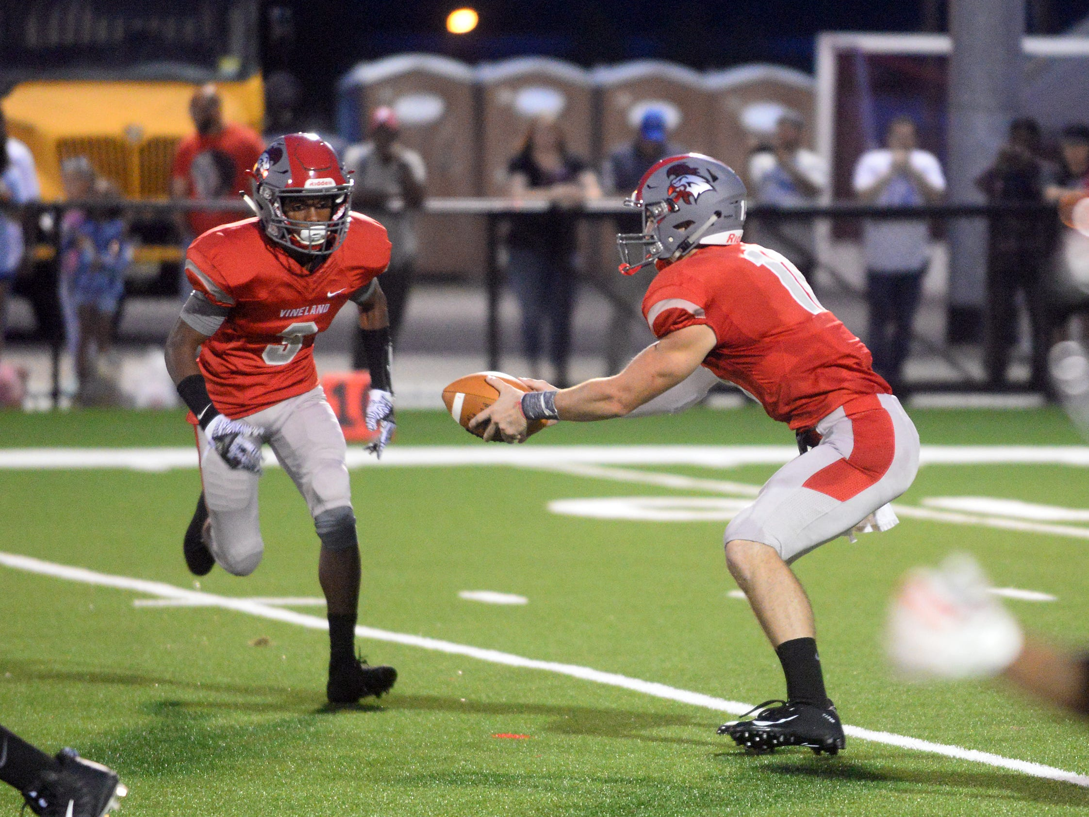 Vineland's QB Ryan Shelton (10) hands the ball off to Jonathan Toney Jr. (3) during a game against Williamstown. The visiting Braves topped The Fighting Clan 24-7 on Friday, August 31.