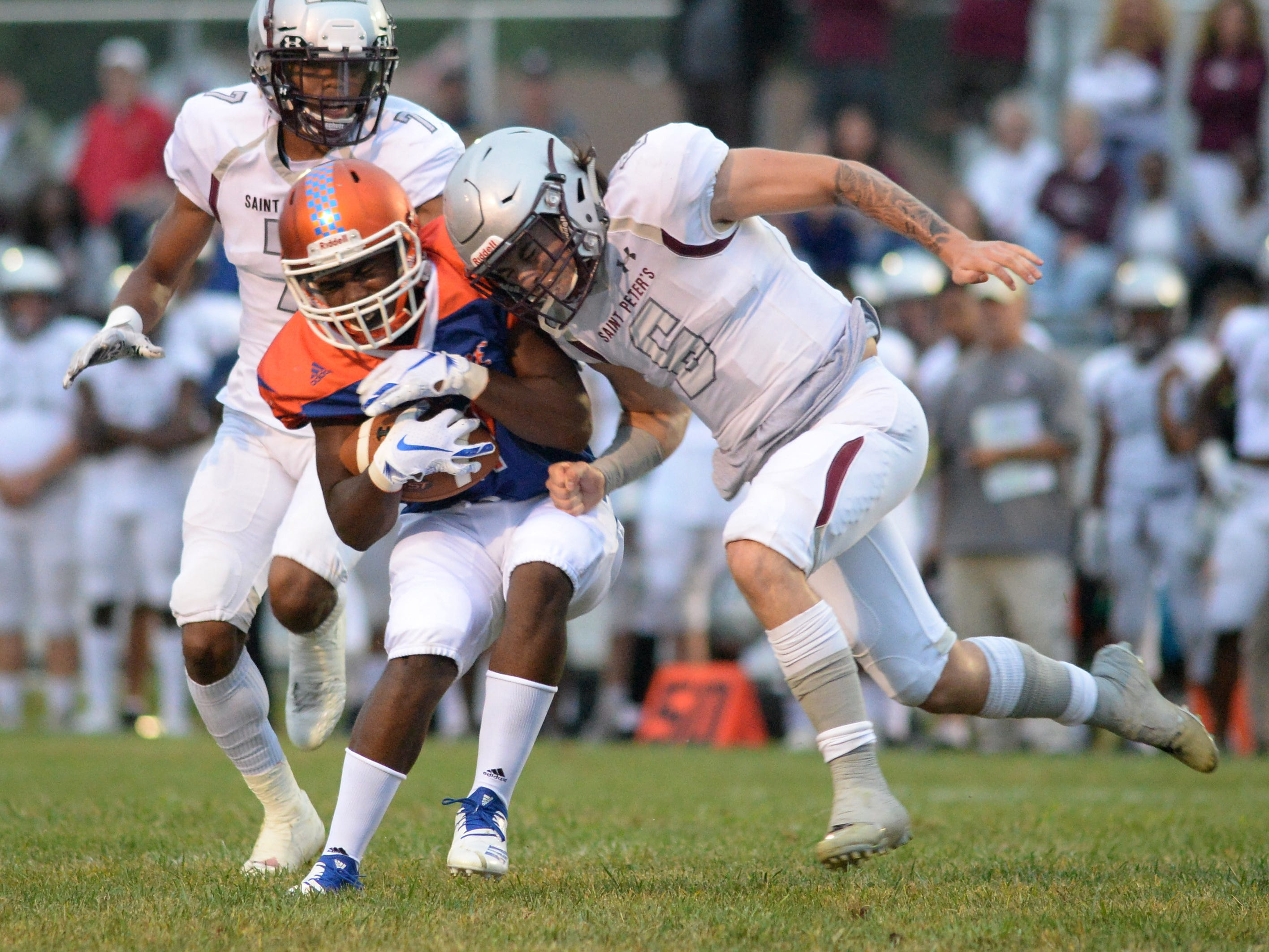 Millville's Dashon Byers is hit by St. Peter's Prep's JJ Scocco as he carries the ball during the season opening football game at Millville Memorial High School, Friday, Aug. 31, 2018.