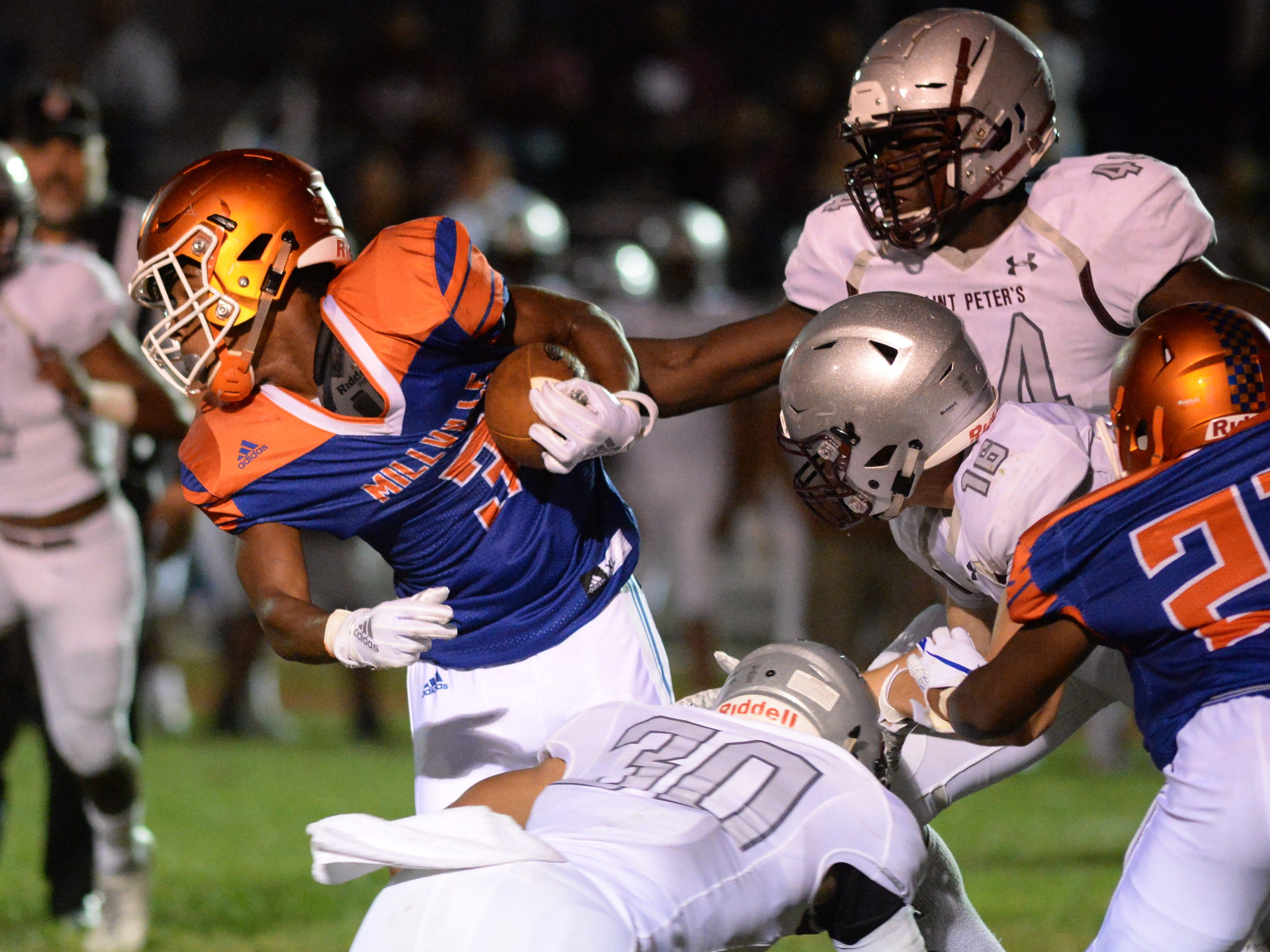 Millville's Cartier Gray breaks a St. Peter's Prep tackle as he carries the ball during the season opening football game at Millville Memorial High School, Friday, Aug. 31, 2018.