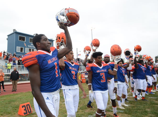 Millville players raise their helmets as the national anthem is played before the season opening football game against St. Peter's Prep at Millville Memorial High School, Friday, Aug. 31, 2018.