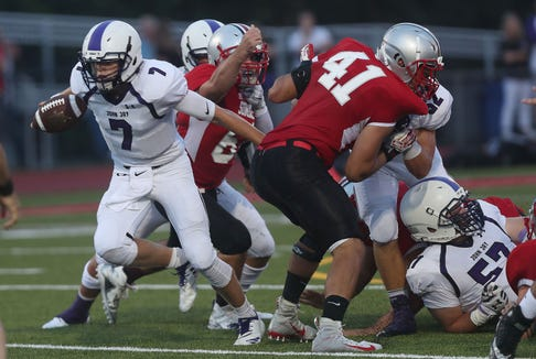 John Jay's Bryce Ford (7) looks for some running room in the Somers defense  during opening night football action at Somers High School Aug. 31, 2018. John Jay won the game 34-20.