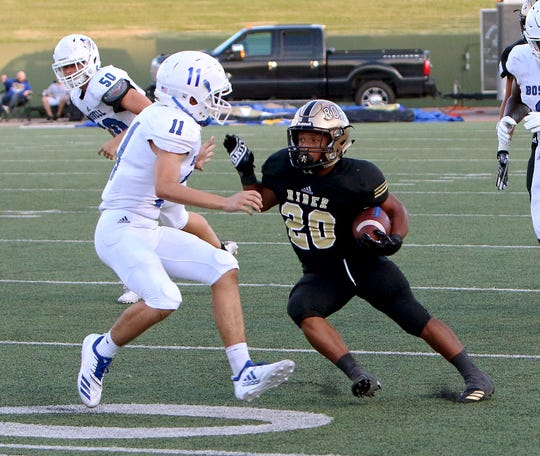 Rider's Tre Byrd (20) cuts back away from Boswell's Toby Fuller (11) on Friday, Aug. 31, 2018, at Memorial Stadium.