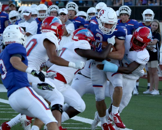 Graham's Chase Gilmore is tackled by Hirschi defenders Friday Aug. 31, 2018, at Graham's Newton Field.