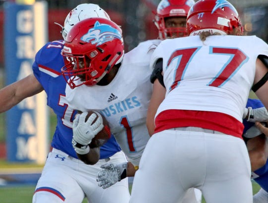 Hirschi's Daimarqua Foster is tackled by Graham defenders Friday Aug. 31, 2018, at Graham's Newton Field.
