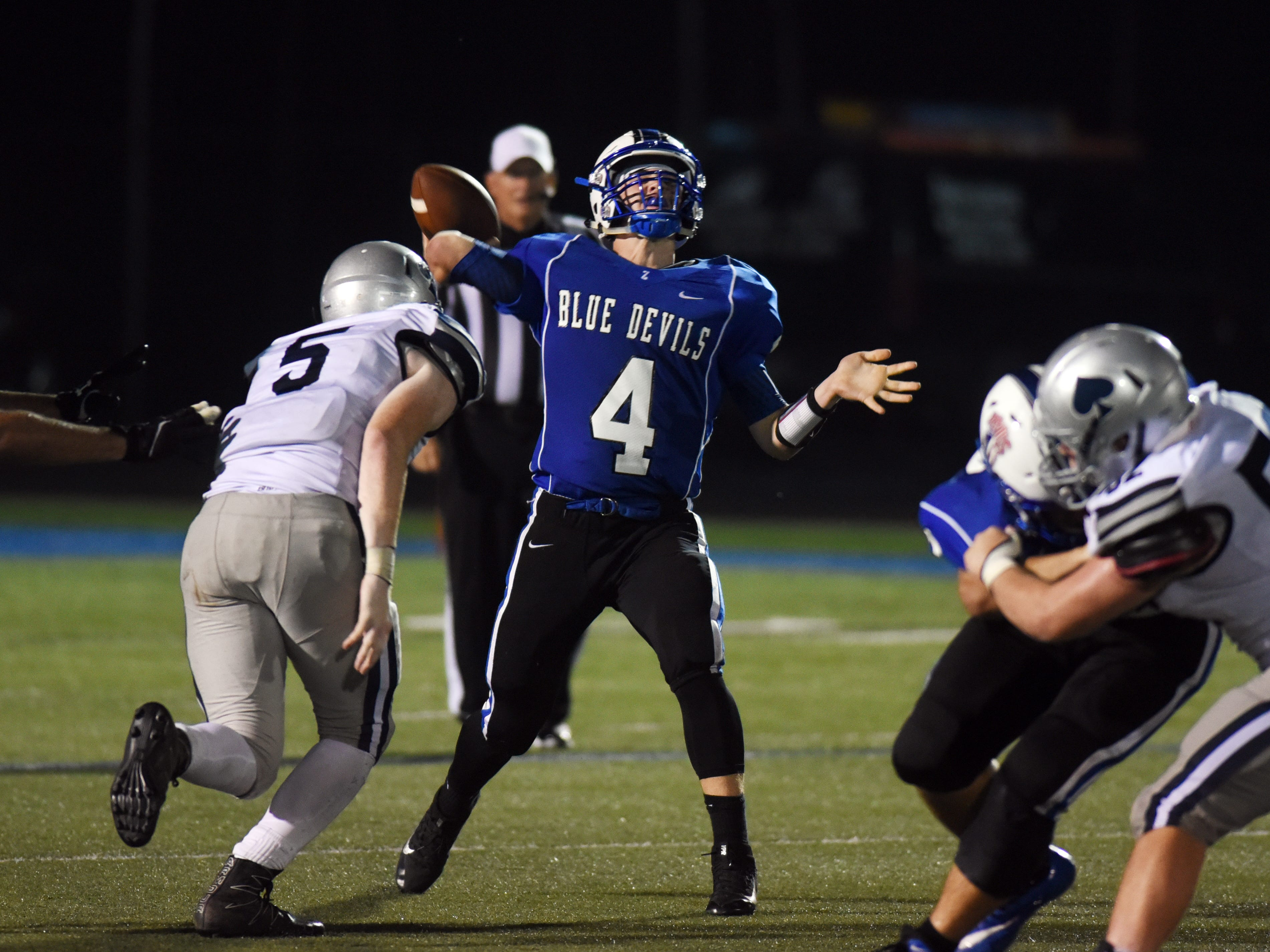 Granville defensive end Garrett Sutliff pressures Zanesville quarterback Ben Everson Friday, during the Blue Aces' 17-14 win in John D. Sulsberger Memorial Stadium.