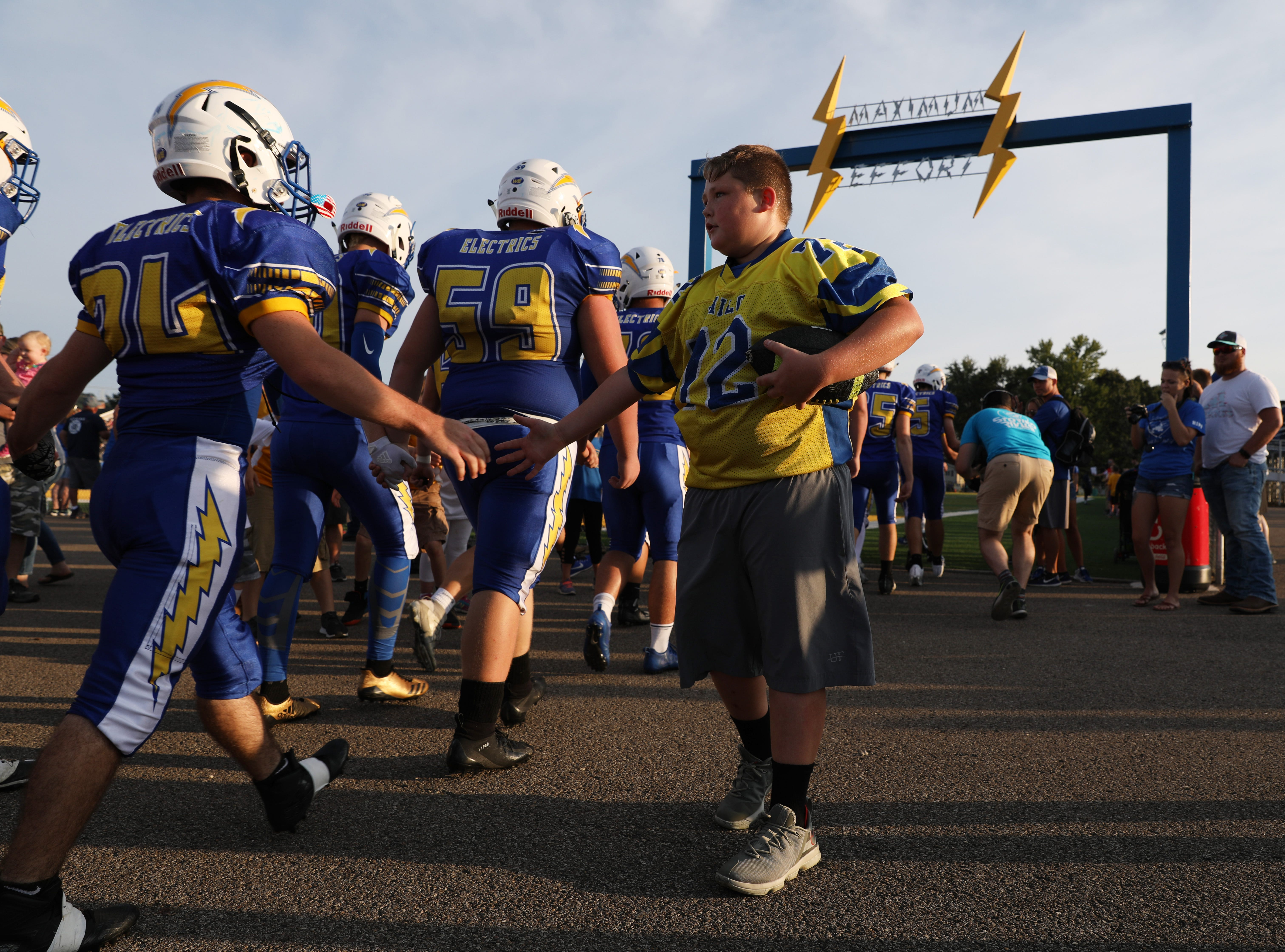 A youngster gets a high five as the Electrics take the field.