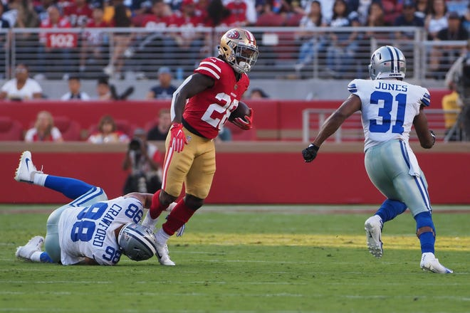 San Francisco 49ers running back Jerick McKinnon (28) escapes Dallas Cowboys defensive end Tyrone Crawford (98) before being tackles by cornerback Byron Jones (31) during the first quarter at Levi's Stadium.