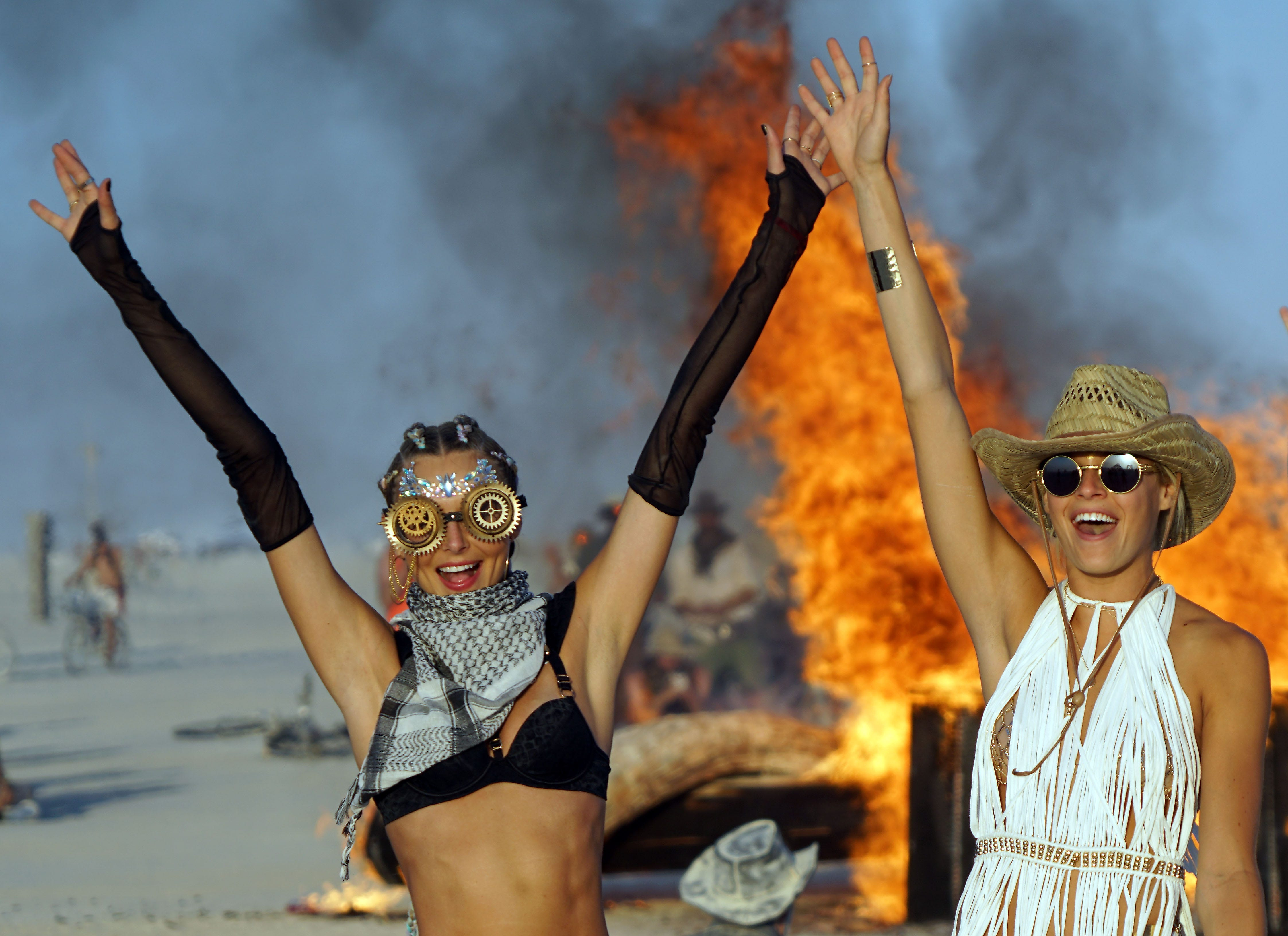 Models Ludi Delfino and Abby Neff pose for photos in front of a burning piece of artwork at Burning Man Aug 31, 2018.