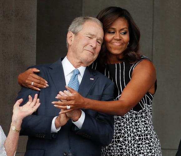 Former first lady Michelle Obama hugs former President George W. Bush during the dedication ceremony for the Smithsonian Museum of African American History and Culture in 2016.