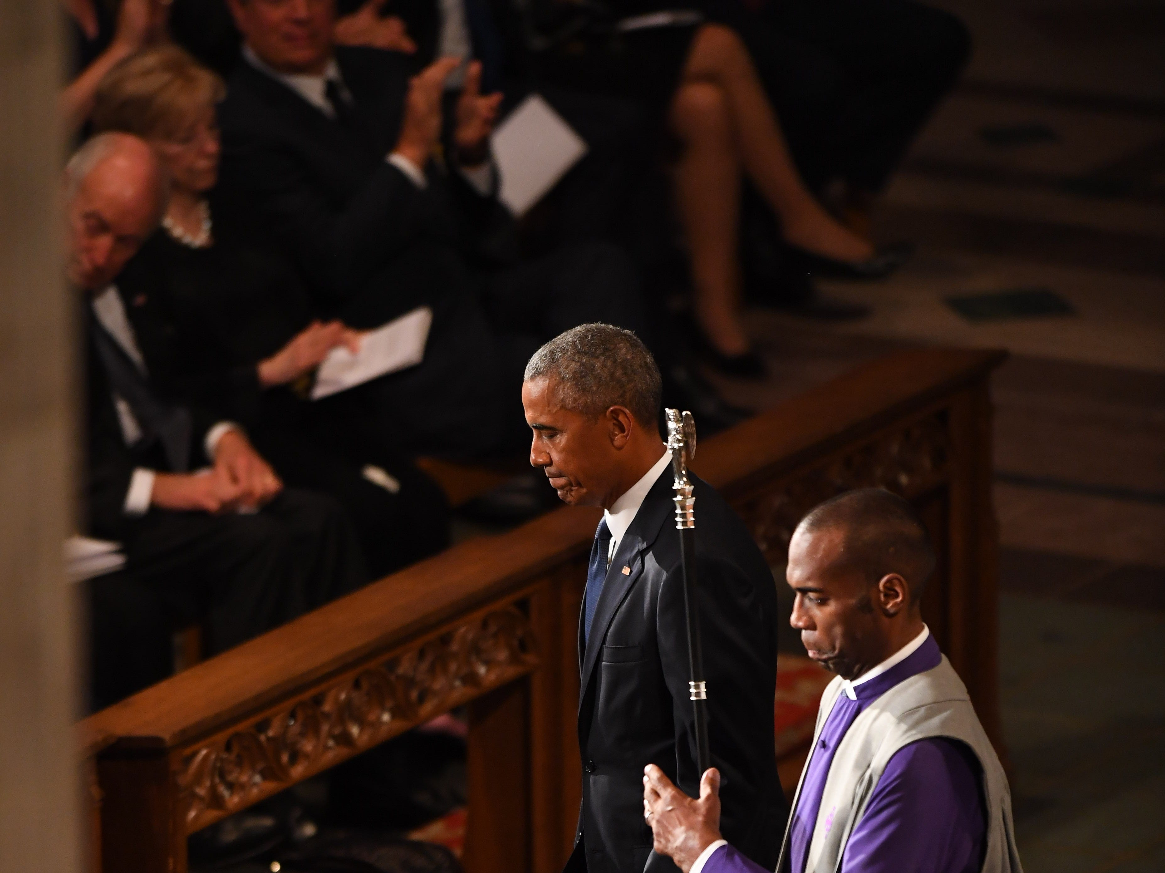 Former President Barack Obama is ushered back to his seat after his words at the memorial service for John McCain.