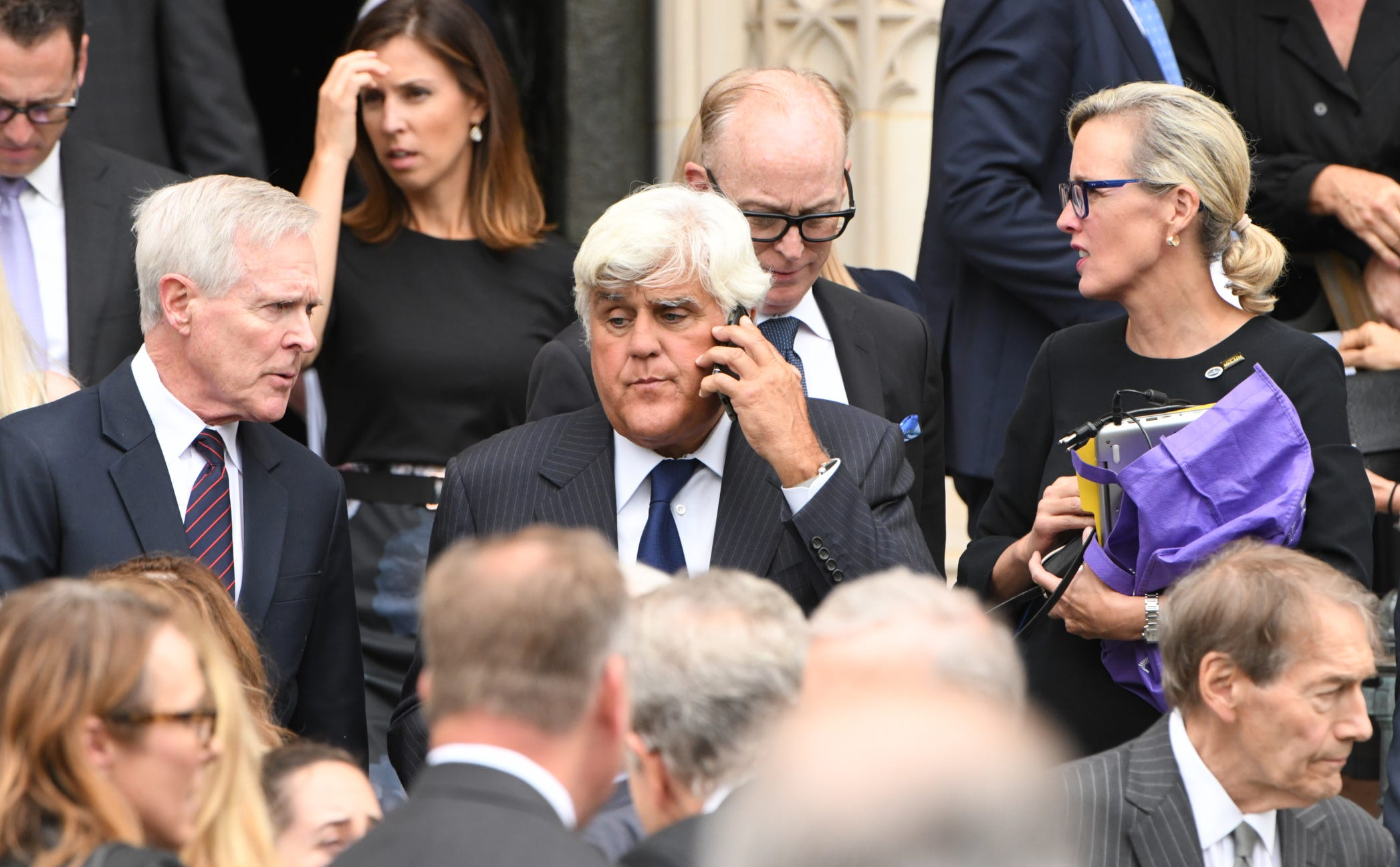 Jay Leno makes a phone call as he leaves the memorial service for John McCain.