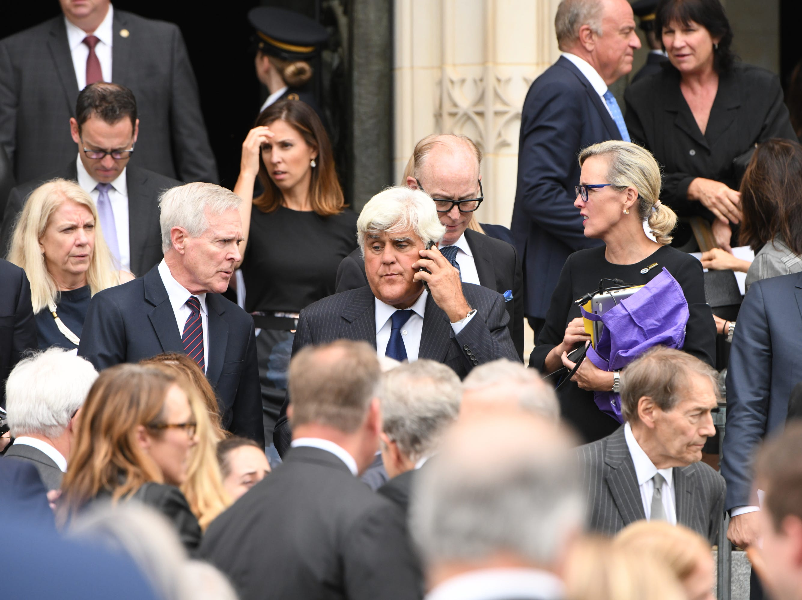 ay Leno makes a phone call as he leaves the memorial service for John McCain.