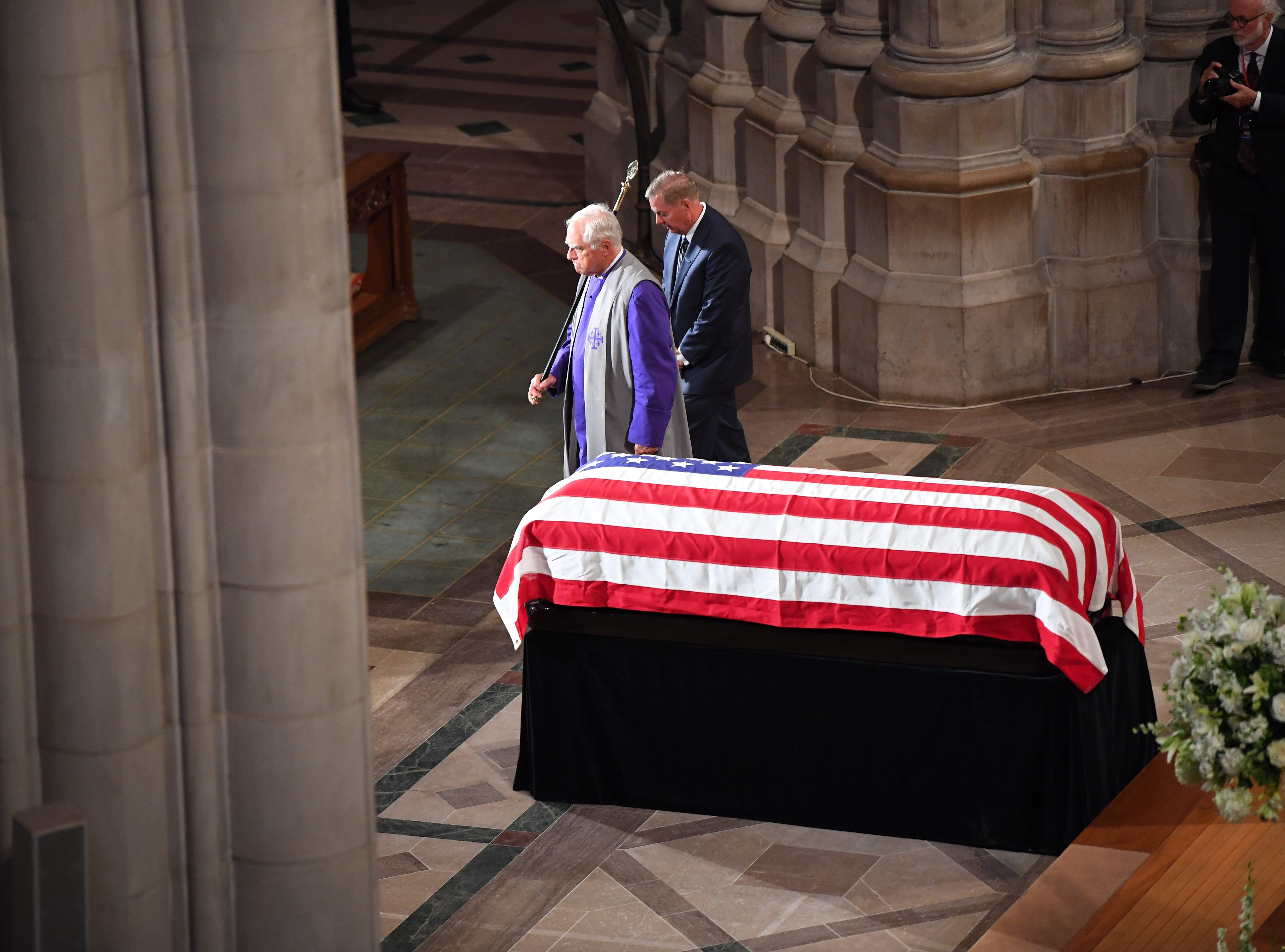 Lindsey Graham returns, Saturday, to his seat after reading the scripture at the memorial service for John McCain.