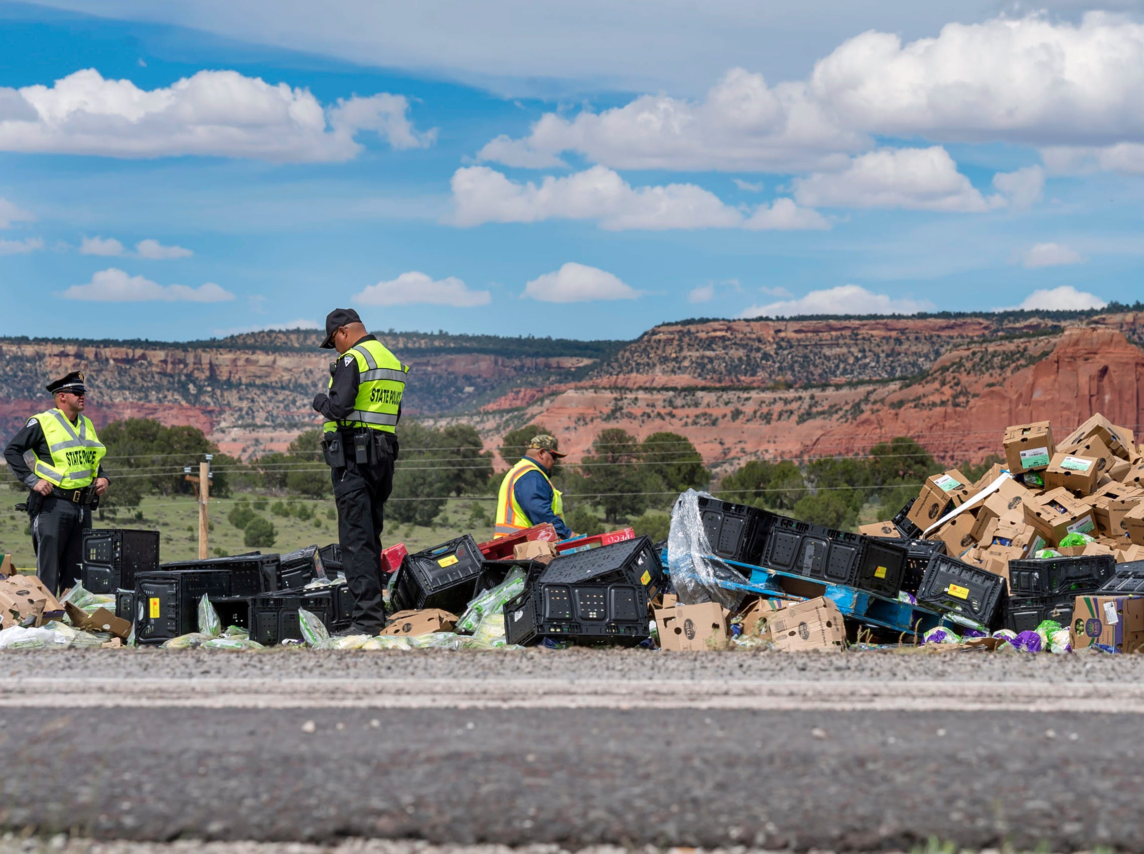 Investigators examine the scene, Thursday,  of the collision of a semitruck that crossed the median of Interstate 40 and crashed head-on into a Greyhound bus near Thoreau, N.M.