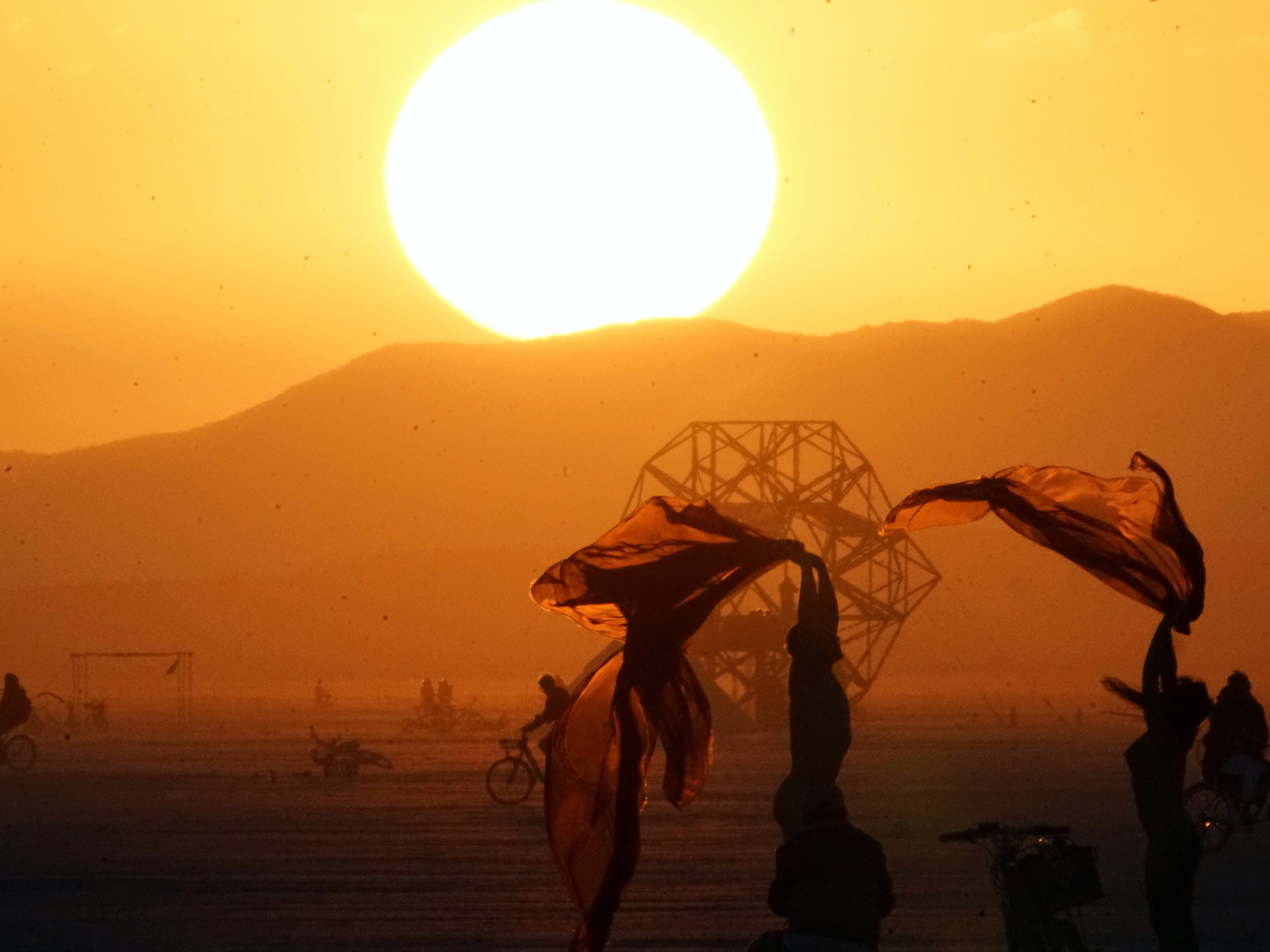 Burning Man attendees conduct a photo session as the sun rises above the horizon Aug. 31, 2018.