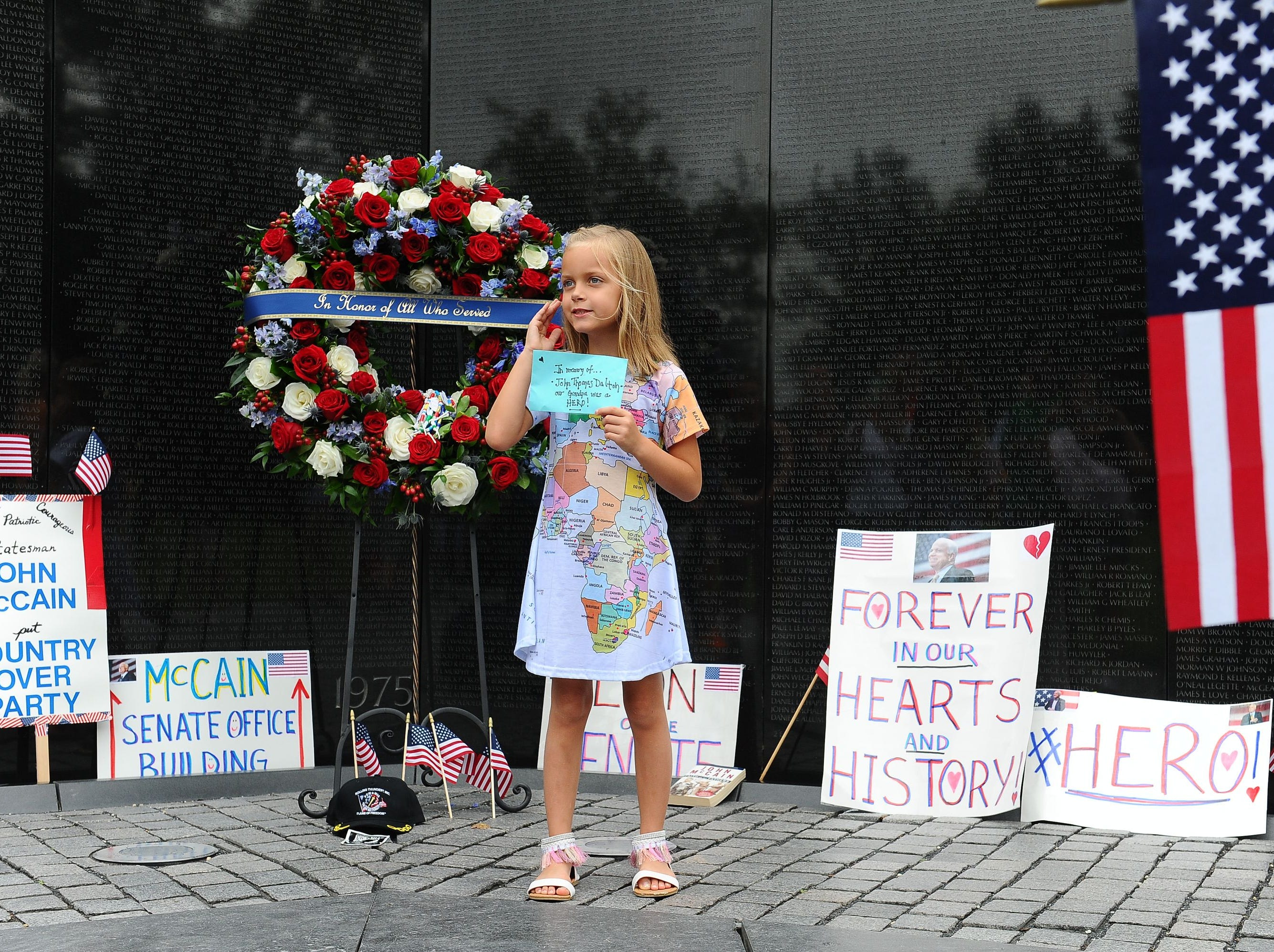 Eliana Duy, 8, stands in front of the wreath that Cindy McCain, wife of late Senator John McCain, laid at the Vietnam Veterans Memorial on Saturday, in Washington, DC.