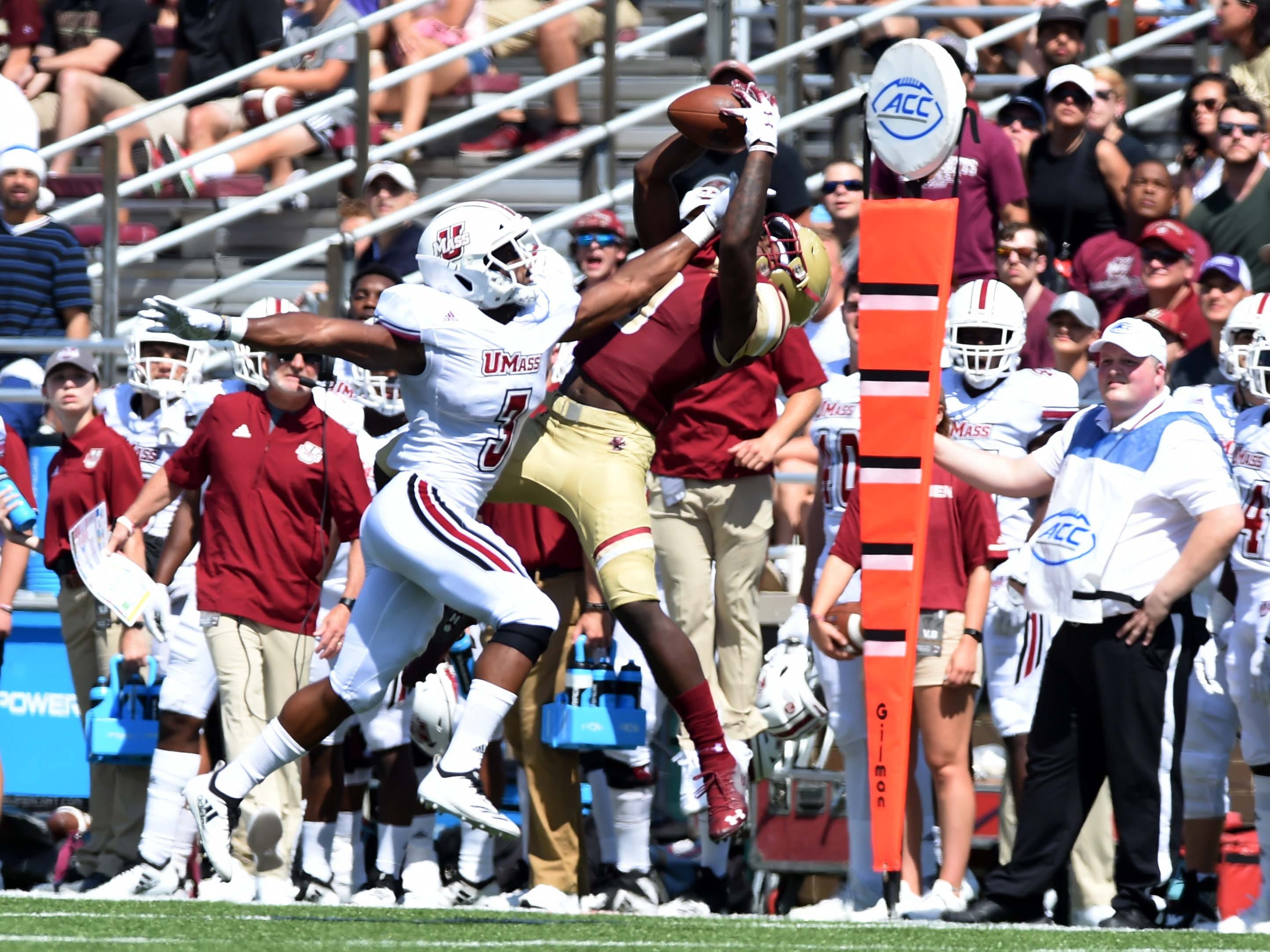 Boston College Eagles wide receiver Kobay White leaps high to match the catch against Massachusetts cornerback Lee Moses.