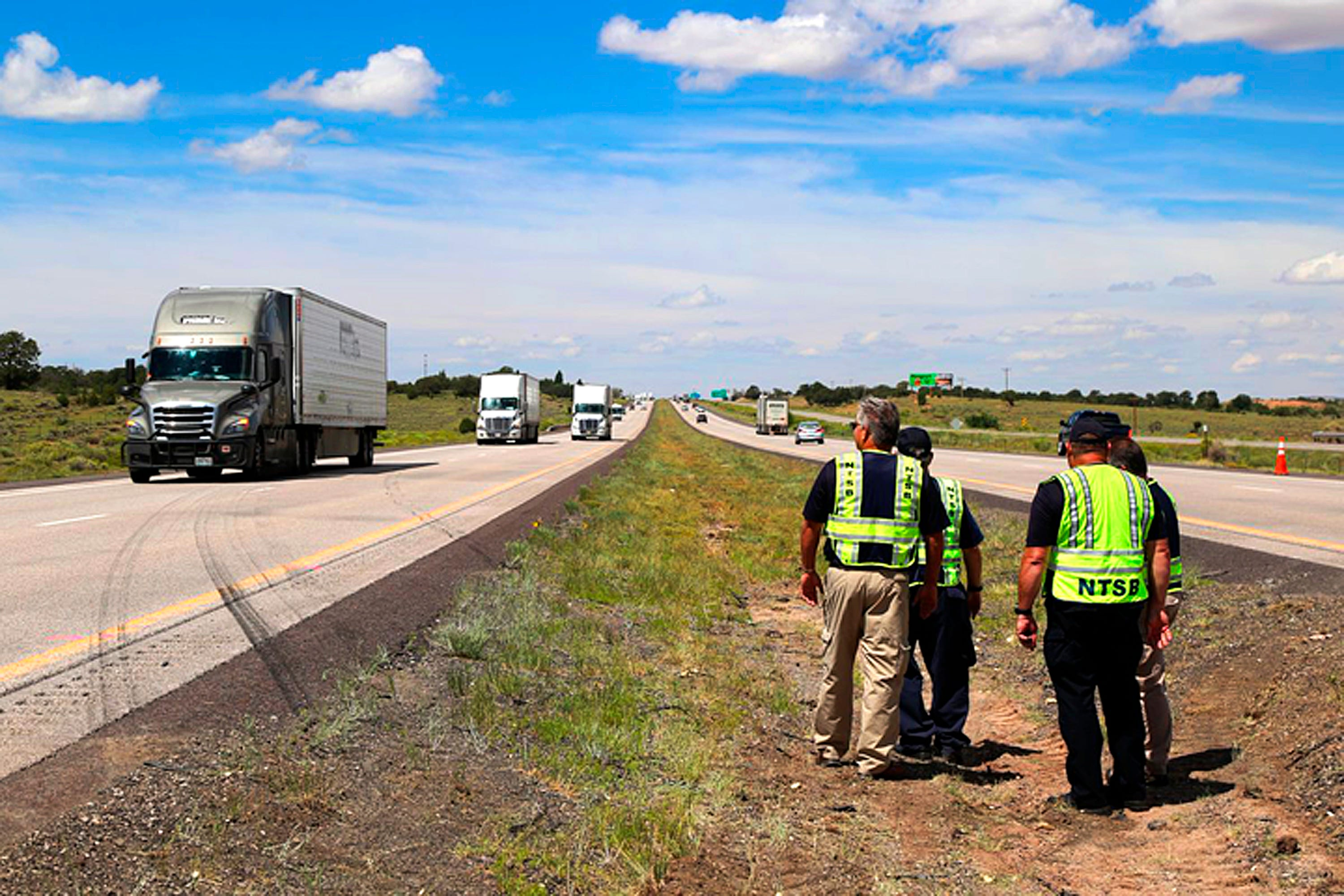This photo provided by the National Transportation Safety Board shows investigators Friday, Aug. 31, 2018, viewing skid marks left by an eastbound big rig when it blew a tire, crossed the median of Interstate 40 and crashed head-on into a westbound Greyhound bus Thursday near Thoreau, N.M. Children were among the dozens of passengers seriously injured in the crash that killed eight people, hospital officials said.