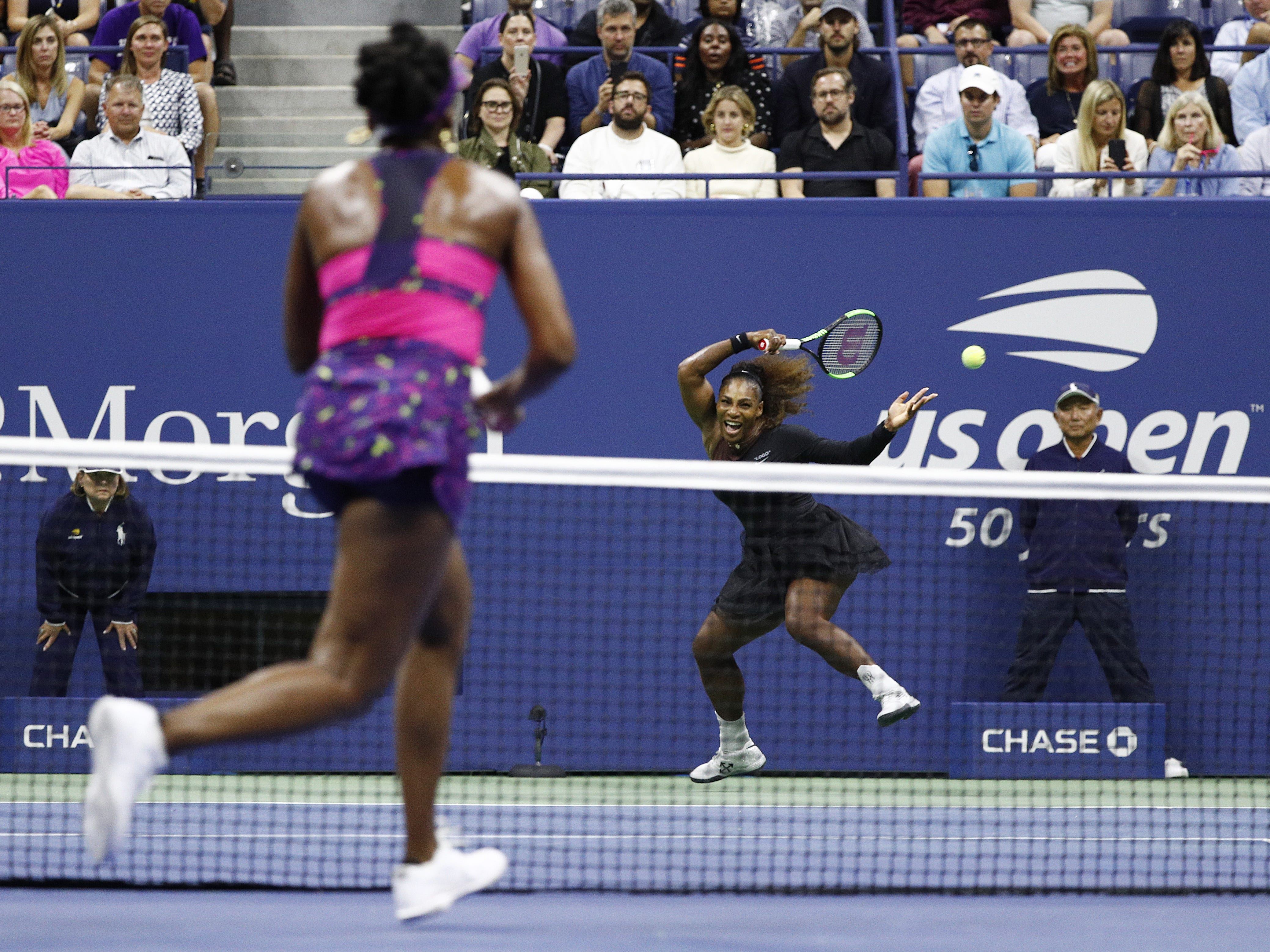 Serena Williams, back, hits a return to sister Venus Williams during their third-round match.
