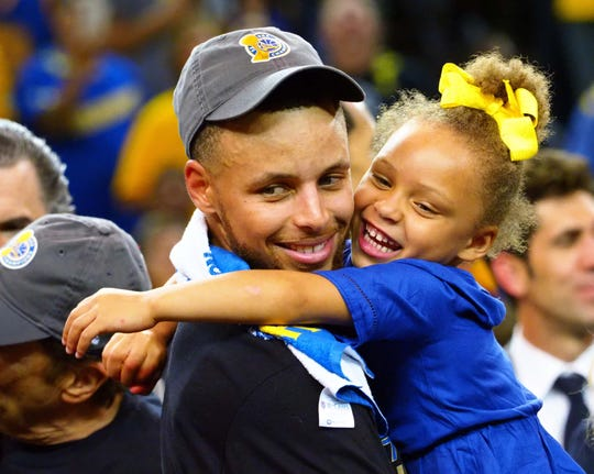 Golden State Warriors guard Stephen Curry (30) celebrates with his daughter Riley Curry after beating the Cleveland Cavaliers in the 2017 NBA Finals at Oracle Arena.