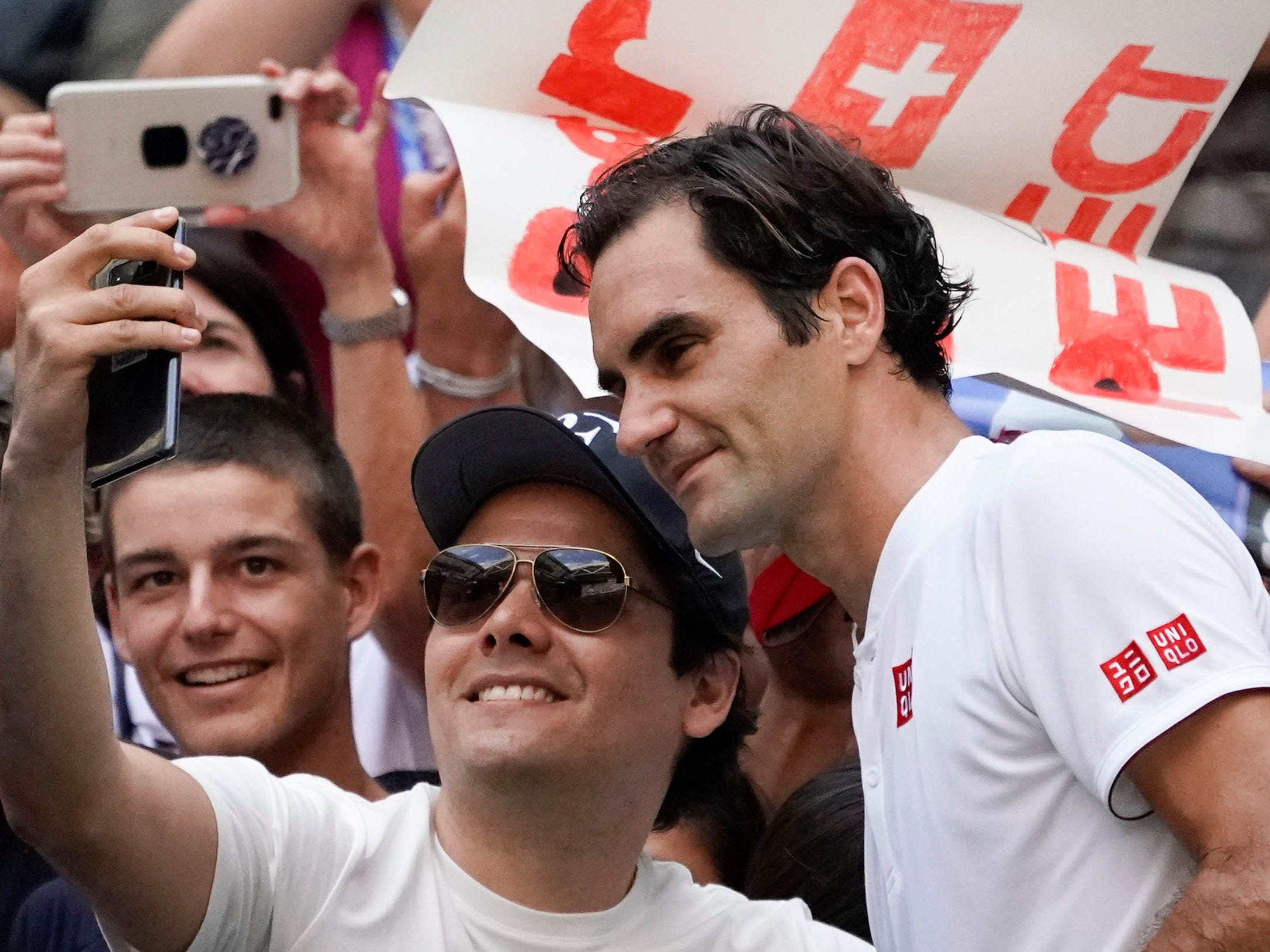 Roger Federer poses with a fan for a selfie after beating Nick Kyrgios in the third round.