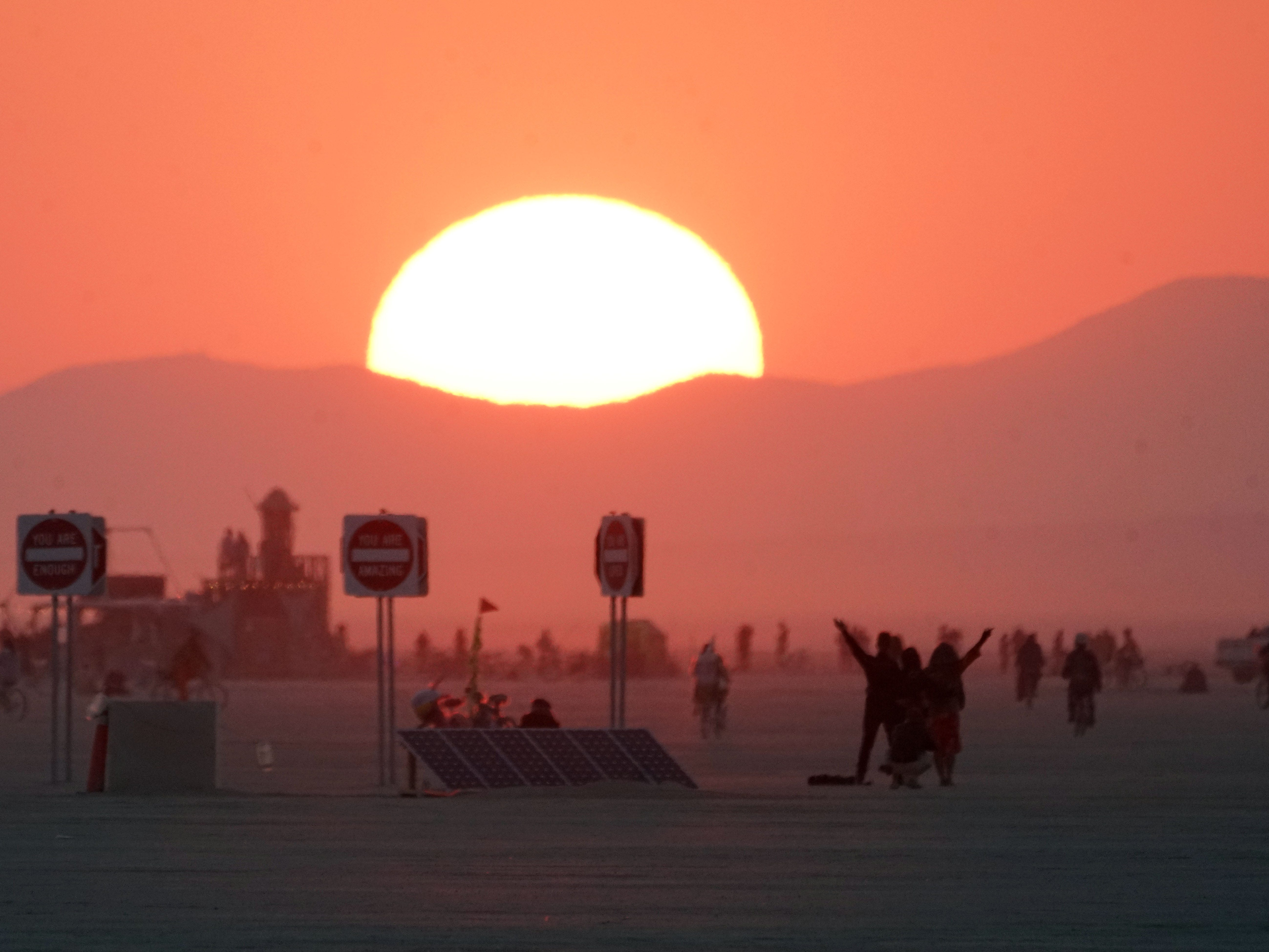 Burning Man participants greet the morning sun on Friday morning after a night of parties and dancing Aug 31, 2018.