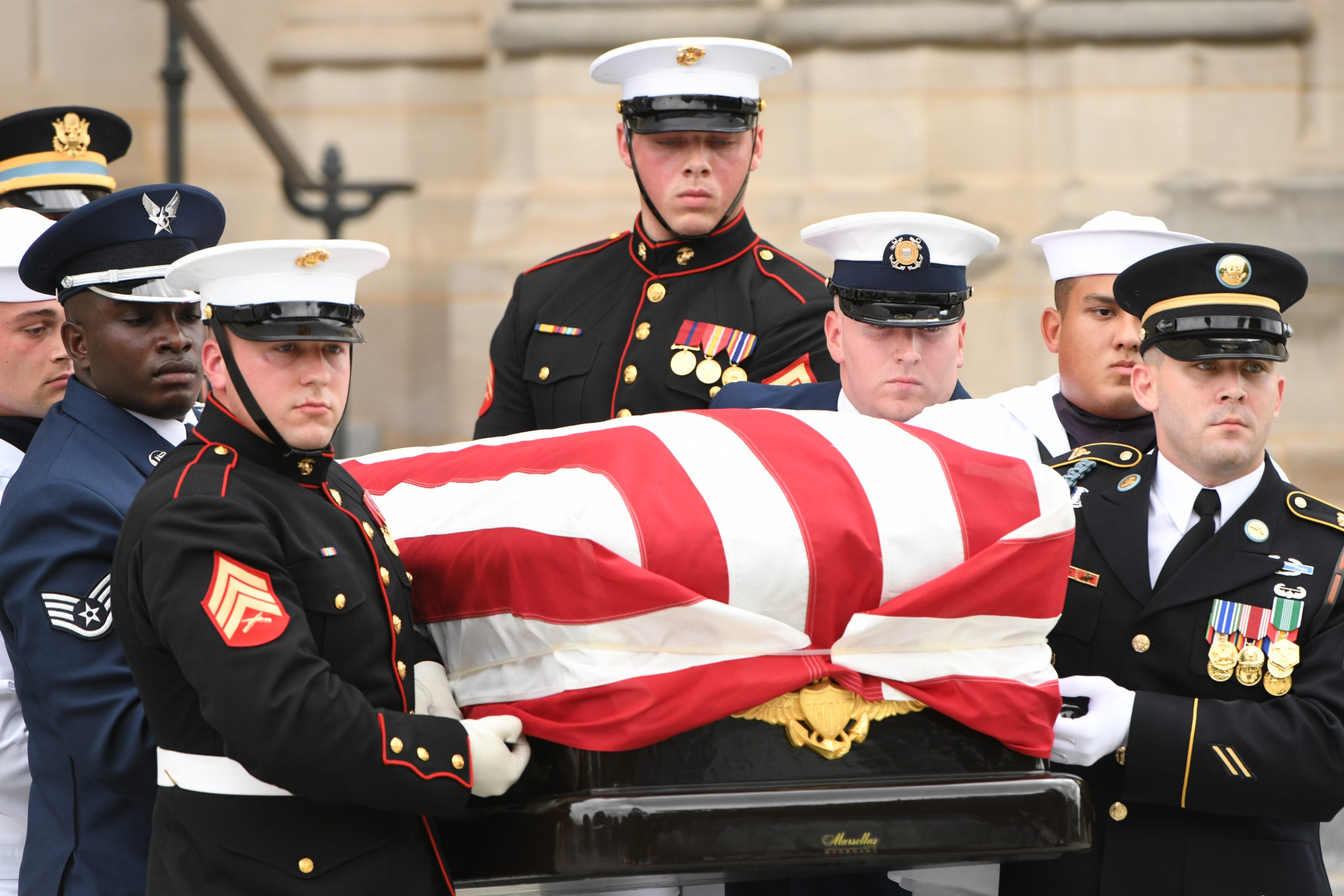 An honor guard team carries the flag-draped casket bearing John McCain from at the National Cathedral, Saturday.