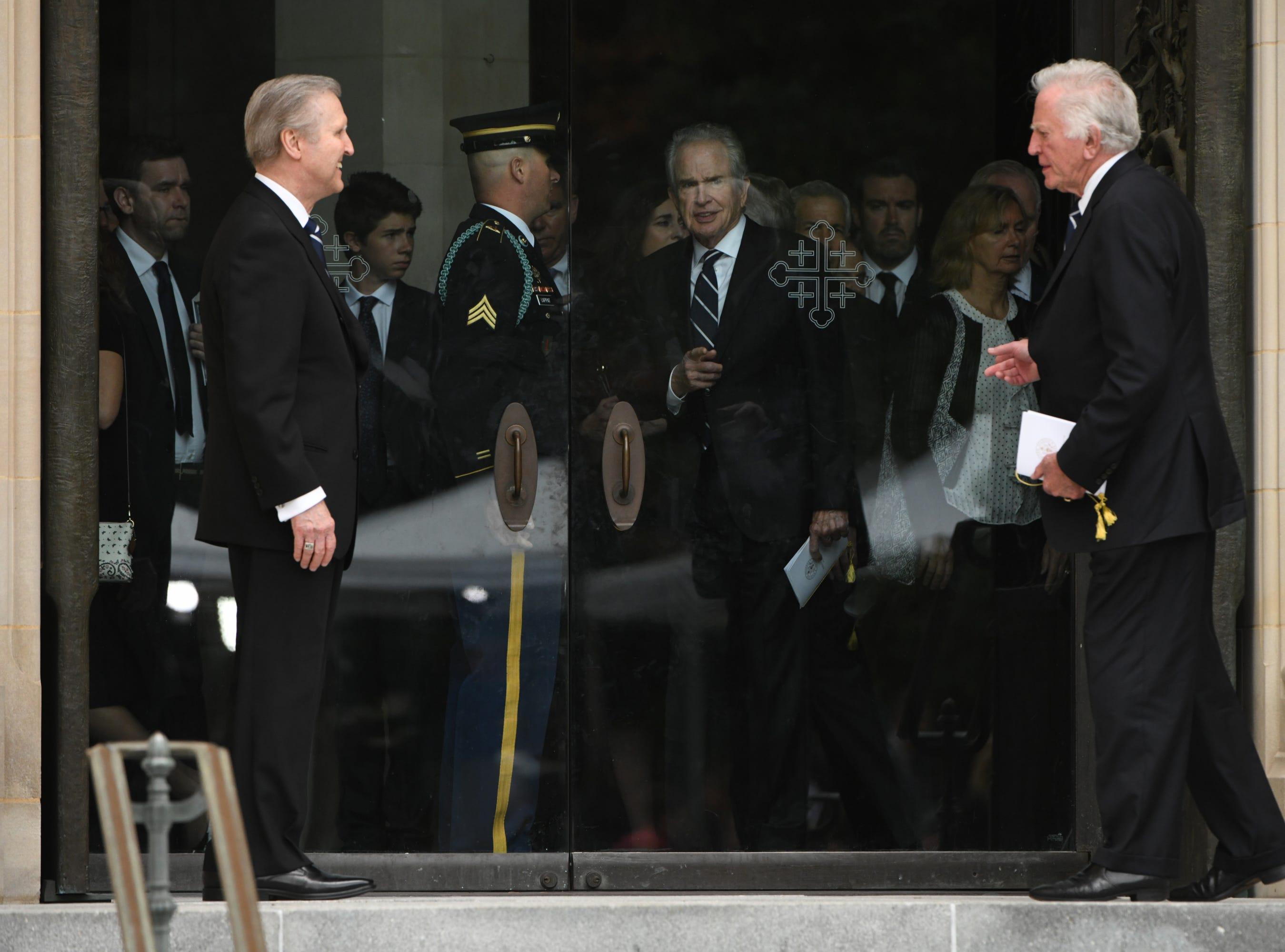 Warren Beatty, center,  greets Former Senator Gary Hart, right, and former Secretary of Defense William Cohen, left, as he leaves the memorial service for John McCain on Saturday.