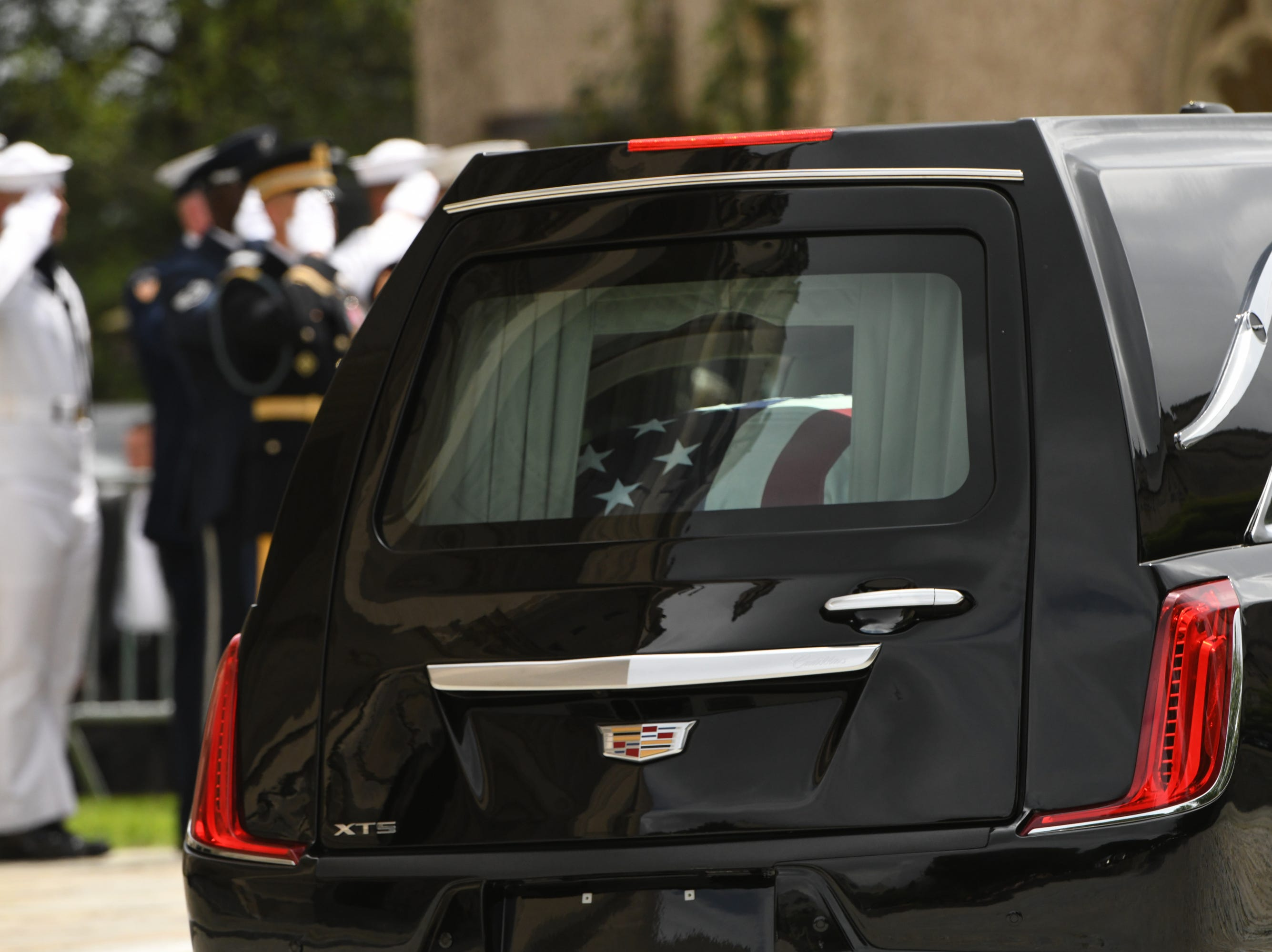 The hearse carrying John McCain leaves the memorial service at the National Cathedral.
