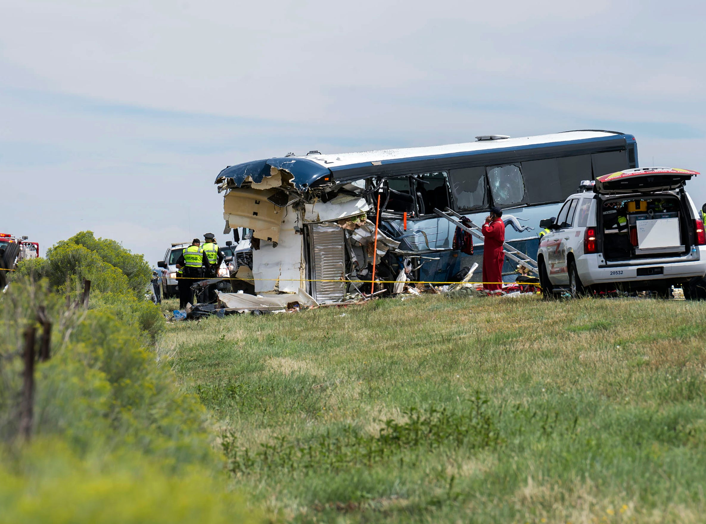 This Thursday, Aug. 30, 2018 photo shows a firefighter at the scene of the collision of a semitrailer that crossed the median of Interstate 40 and crashed head-on into a Greyhound bus near Thoreau, N.M. A California-based trucking company and one of its drivers were accused of negligence Friday in a pair of lawsuits as investigators sorted through the wreckage from a deadly bus crash on a New Mexico highway.
