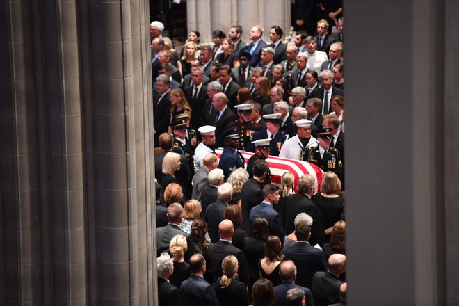 The casket of John McCain is carried by the honor guard for the memorial service at the National Cathedral.