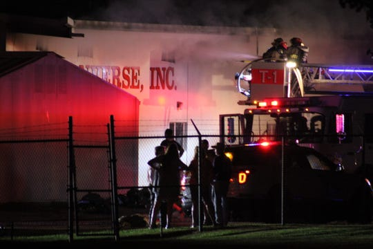 Firefighters direct water to the outside of the Skip Converse Inc. building in Pineville early Sunday. A fire appeared to have heavily damaged the Jones Street business.