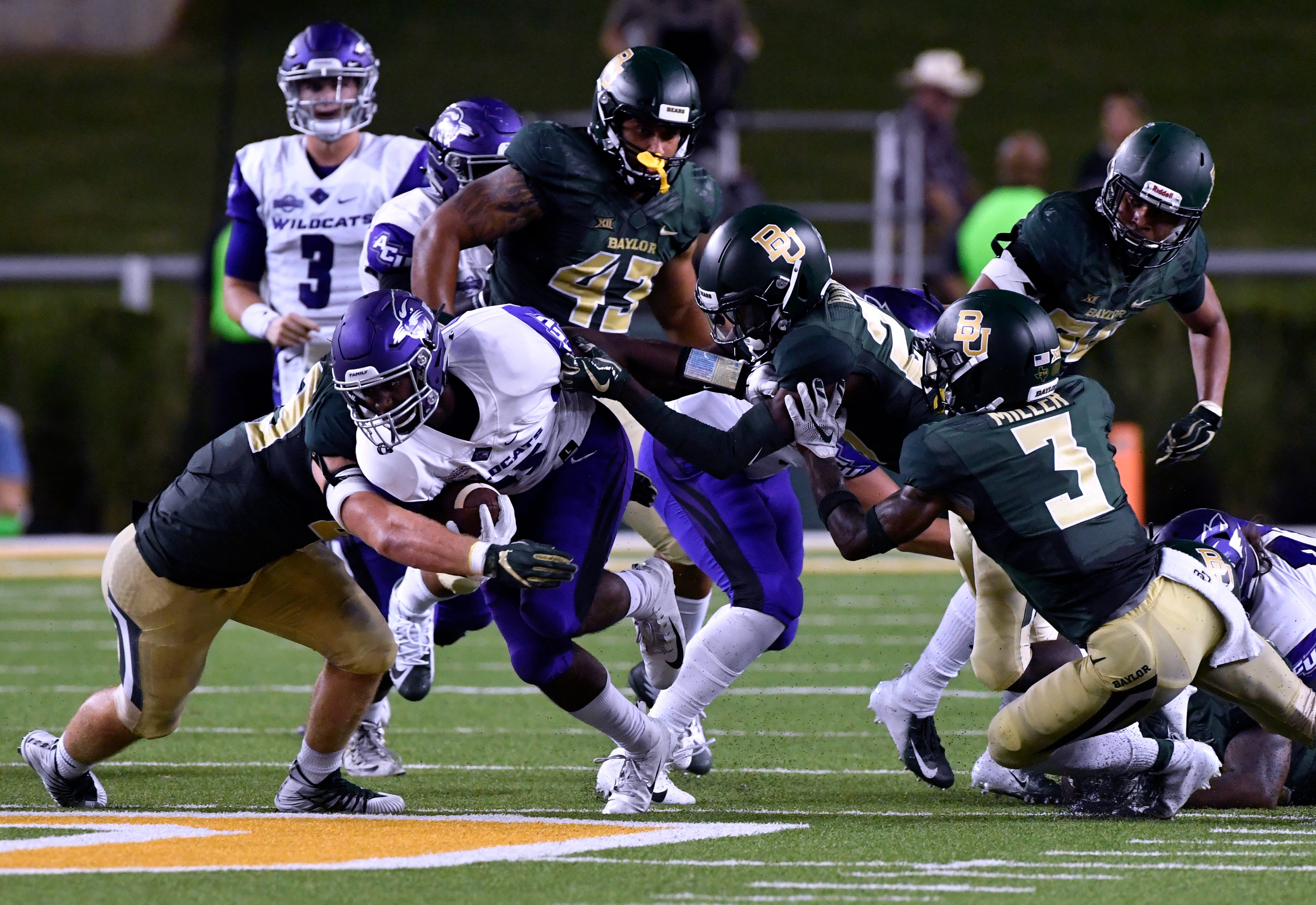Wildcats running back Tyrese White is surrounded by Baylor defenders during the Sept. 1 game in Waco.