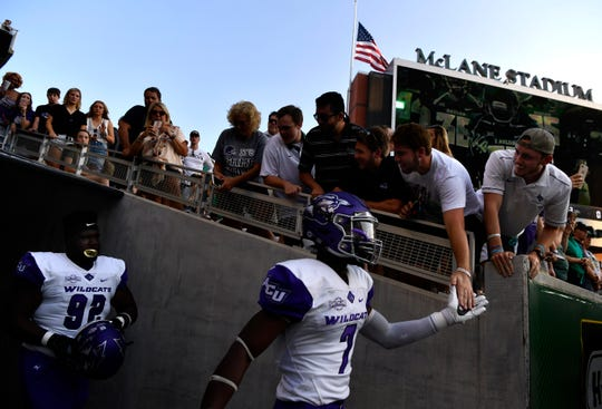 An Abilene Christian University fan slaps palms with safety Bolu Onifade as the Wildcats enter the field before Saturday's game at Baylor University.