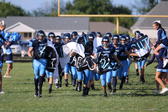 Adena High School's football team runs on to the field in a game against Marion Elgin in 2018.