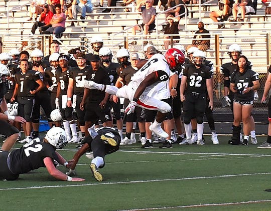 Kings' Nak'emon Williams (6) high hurdles the Lakota East defense as the Knights top the Thunderhawks 27-24 in a two-day weather plagued game, Sept. 1, 2018.