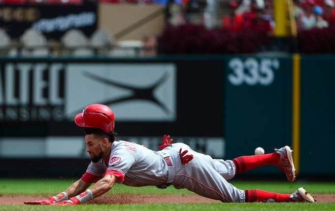 Cincinnati Reds center fielder Billy Hamilton (6) loses his helmet as he slides in for a double during the first inning against the St. Louis Cardinals at Busch Stadium.