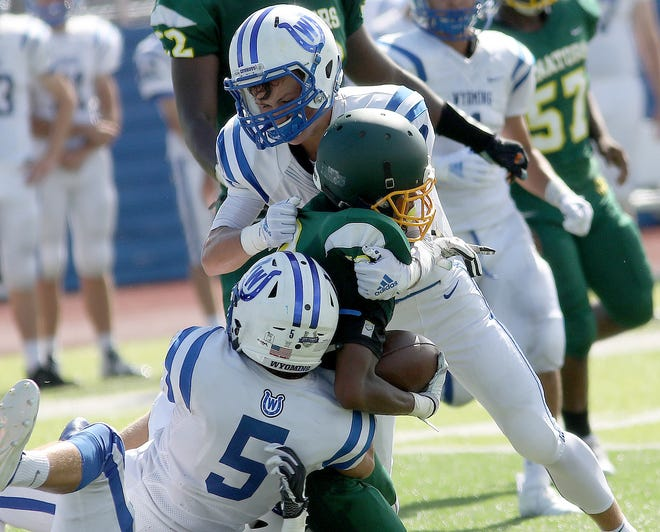 Taft's Mylan Hall is tackled by Wyoming defenders as he runs the ball during the  Senators' 14-12 loss to Cowboys, Saturday, Sept. 1, 2018.