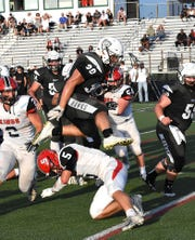 Lakota East's Jack Dobrozsi (30) high jumps Kings' Max McKelvey en route to the endzone for the Thunderhawks, Sept. 1, 2018.
