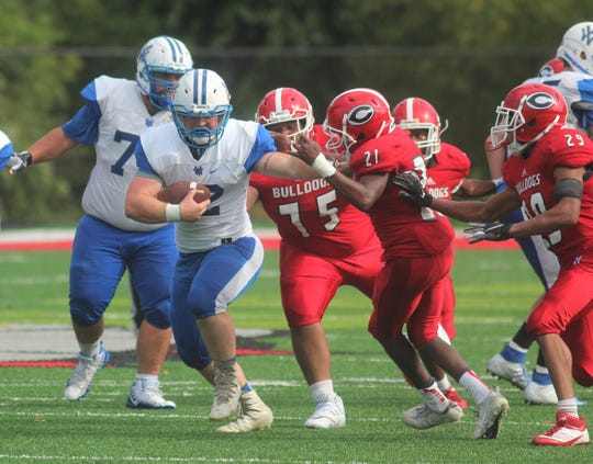 Walton-Verona senior Micah Alford stiff-arms Holmes freshman David Commodore on his way to a strong run during Walton-Verona's 48-0 win over Holmes Sept. 1 at Holmes High School. The game concluded on Saturday morning after being suspended at halftime because of weather.