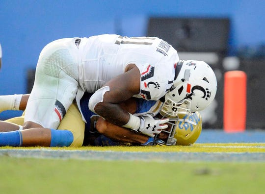 UCLA Bruins tight end Caleb Wilson (81) is brought down by Cincinnati Bearcats linebacker Bryan Wright (11) which results in a safety during the second half at the Rose Bowl.