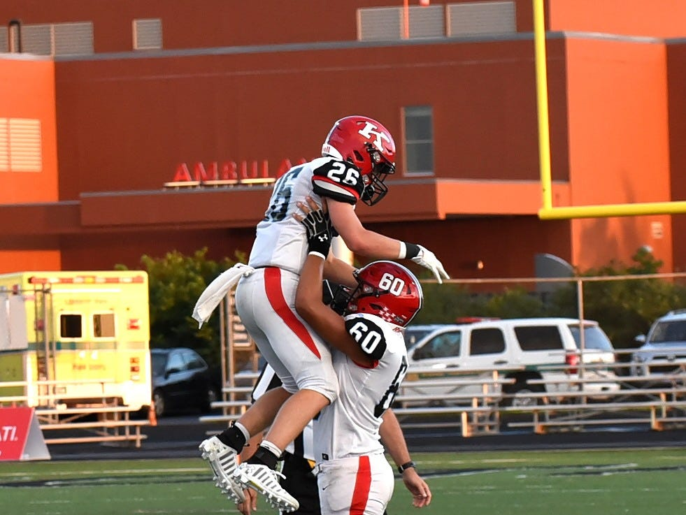 Jaxon Smith (60) of Kings lifts Ty Stylski (26) in the air in excitement as the Knights top Lakota East in comeback fashion, Sept. 1, 2018.
