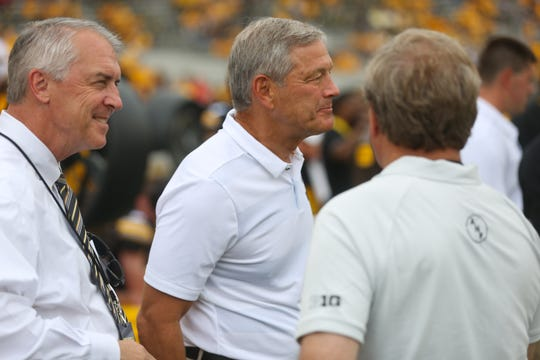 Gary Barta, Kirk Ferentz and Bruce Harreld chat on the sidelines before the Hawkeyes' game against Northern Illinois at Kinnick Stadium on Satuday, Sept. 1, 2018.