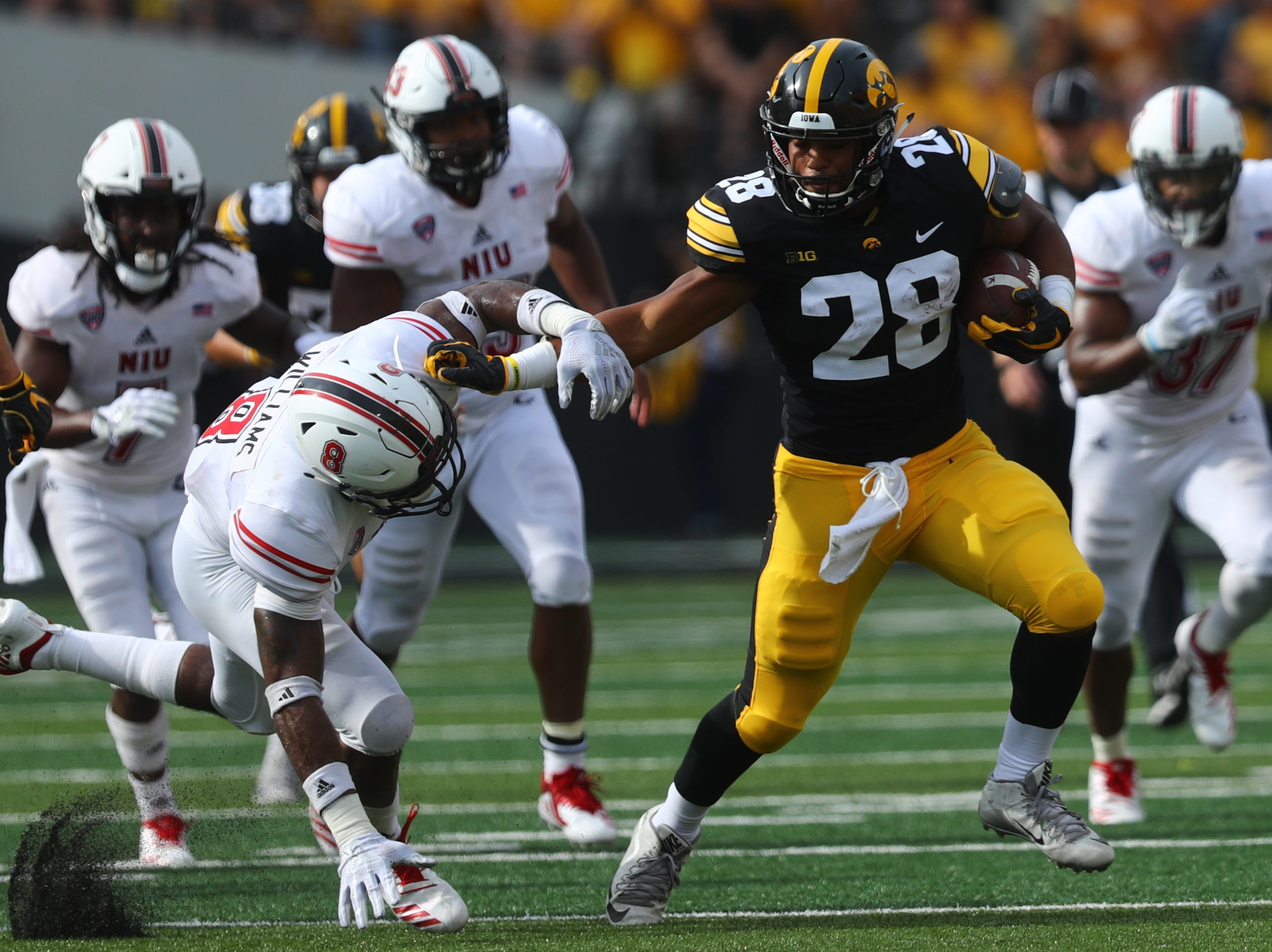 Iowa's Toren Young pushes away Northern Illinois' Mykelti Williams as he runs down field during their game at Kinnick Stadium on Satuday, Sept. 1, 2018.