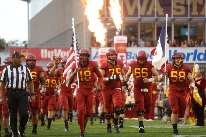 Iowa State wide receiver Hakeem Butler (18) and Iowa State defensive end Spencer Benton (58) carry out the flags Saturday, Sept. 1, 2018, at the start of their game against South Dakota State at Jack Trice Stadium in Ames.