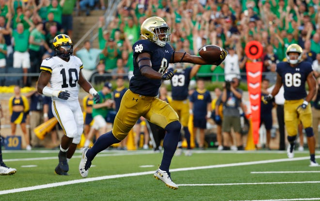 Notre Dame receiver Jafar Armstrong scores a touchdown past Michigan linebacker Devin Bush in the first quarter in South Bend, Ind., Saturday, Sept. 1, 2018.
