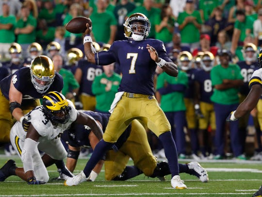 Brandon Wimbush passes as Rashan Gary tries to pressure him in the first half.